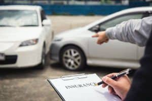 Insurance adjuster taking notes after a car accident